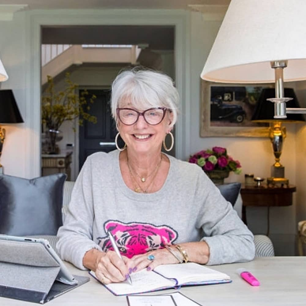 Maggie Macmillan Remenham Hill office woman at desk wearing grey jumper with pink tiger on it