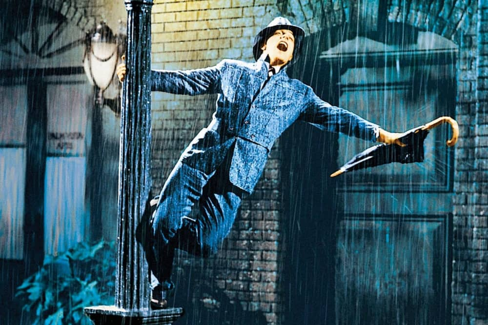 Singing In the Rain Gene Kelly hanging from lampost holding umbrella