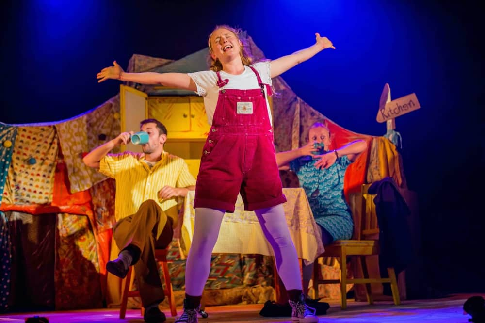 The Bear Pijns and Needles production main character Tilly in short dungareers singing and dancing