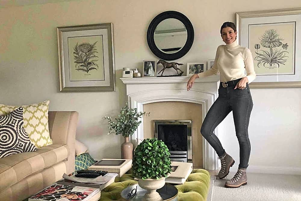 Victoria Morris Ascot woman leaning against living room fireplace