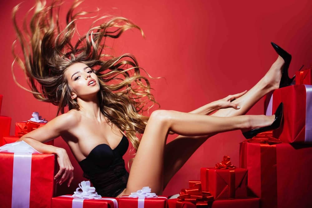 Fashion model in black heels and basque draped over red gift boxes – christmas shopping