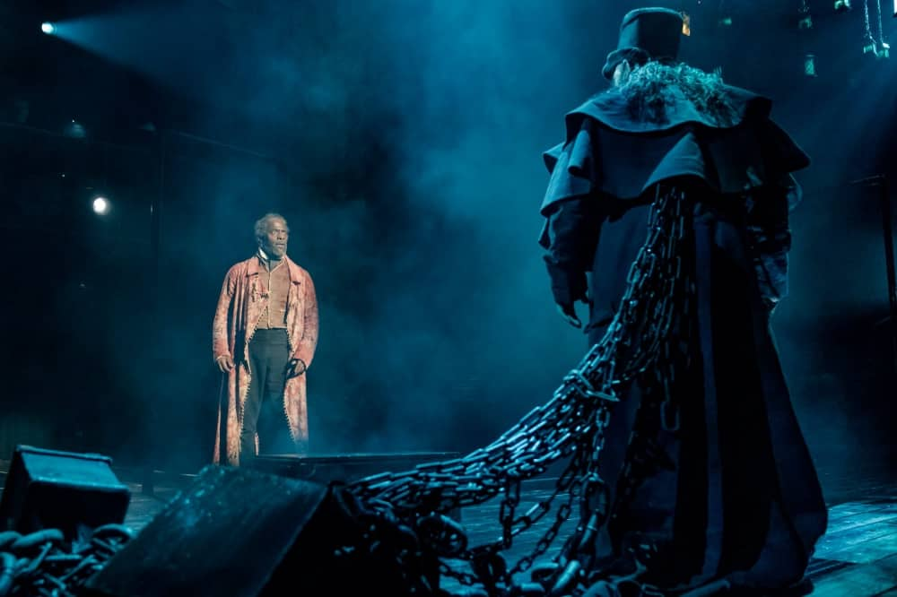 A Christmas Carol Old Vic 2019 – scrooge meets the ghost wearing black overcoat hat and heavy chains
