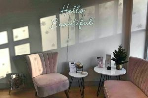 Bridge Street Skin Clini waiting area blush pink velvet sofa and chair neon hello beautiful wall art