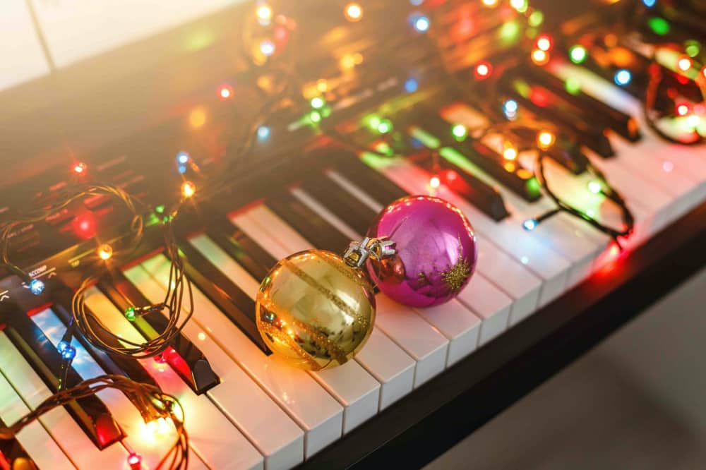 Christmas Carols Singing piano with christmas lights and baulbles on the keys