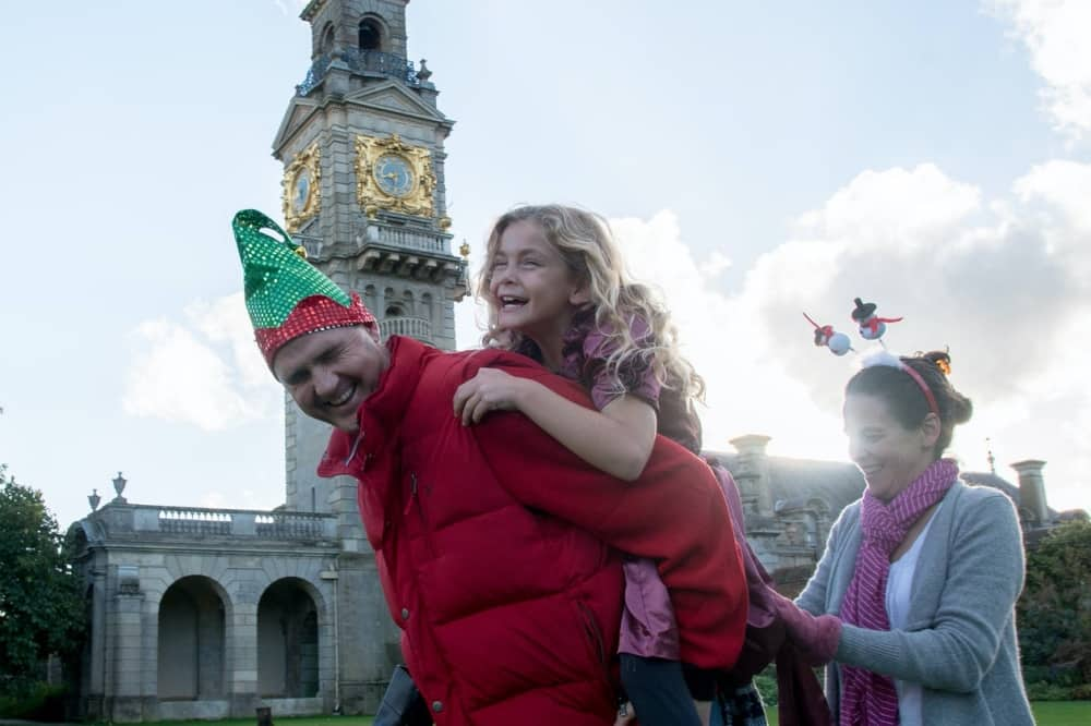 Cliveden Festive Trail elf hat wearing man gives girl piggy bag, mum follows in festive deeliboppers