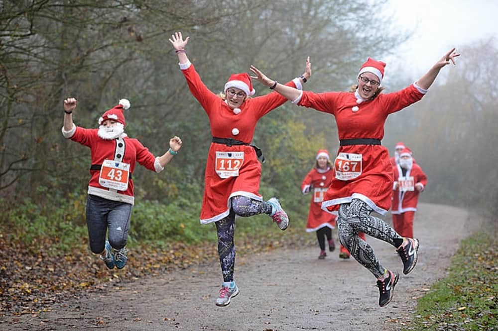 Dinton Pastures Berkshire Santa Dash women in santa outfits running and clicking their heels