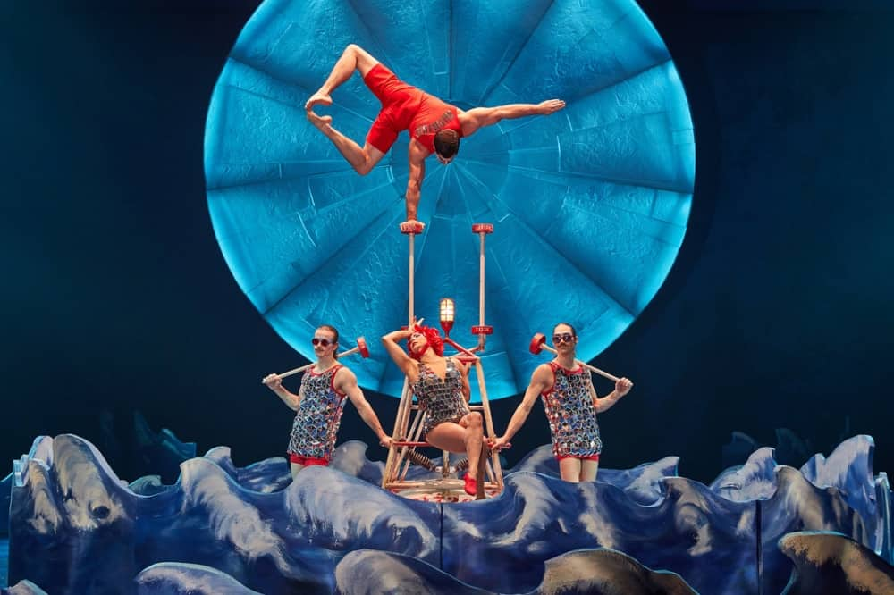 Luzia Cirque Du Soleil performers in stage of sea with acrobats balancing above the water