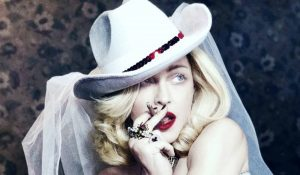 Madame X Madonna wearing cowboy hat with veil smoking a cigar