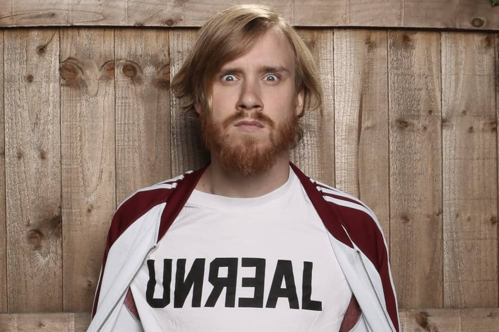 Comedian Bobby Mair fair hair, beard wearing retro track top and UNREAL slogan t shirt