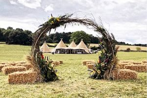 Forest Edge Tipis Berkshire outdoor wedding/party venue seen through willow and floral arch