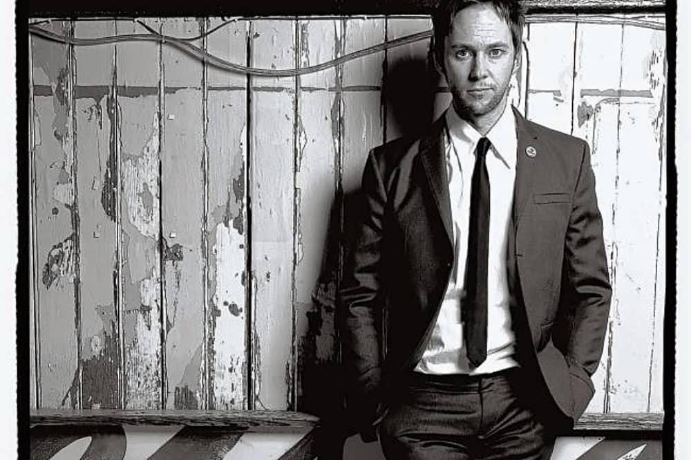 James Redmond Comedian black whote photo weaerinf suit and leaning against wood pannelled wall
