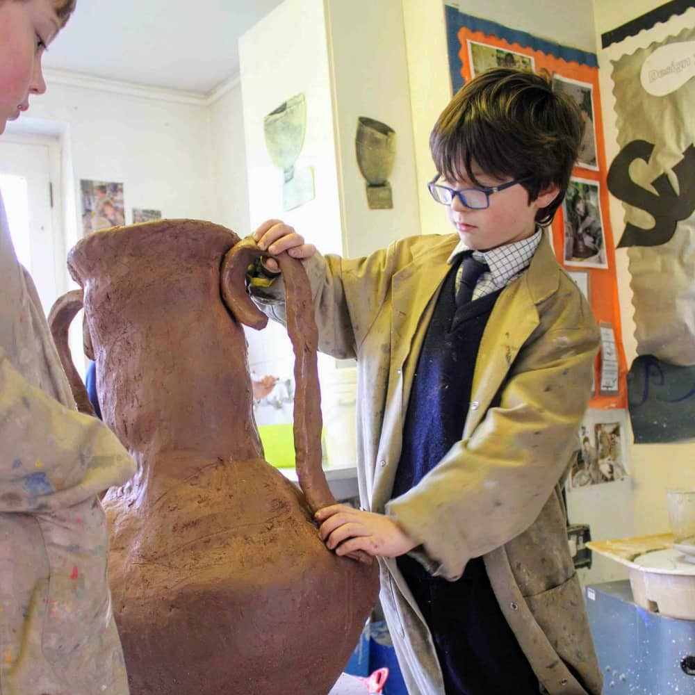 Ludgrover School pottery class boy wearing glasses makes large Greek urn