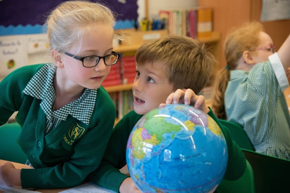 Waverley pupils boy and girl looking at a globe in geography