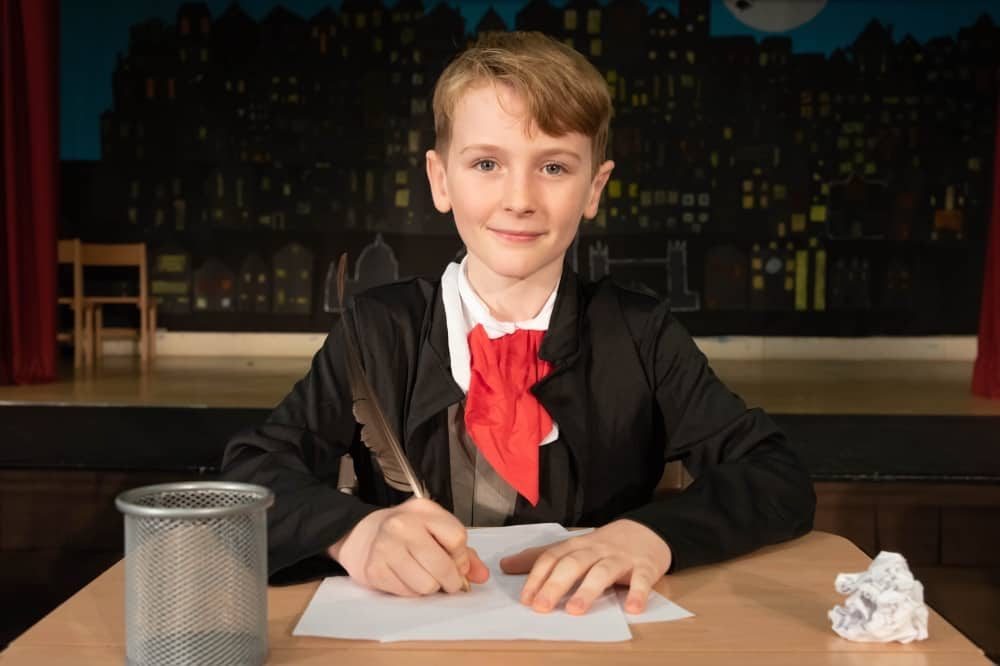 Waverley Prep School KS2 Bob Cratchett dressed as ebonezer scrooge with feather quill writing at desk