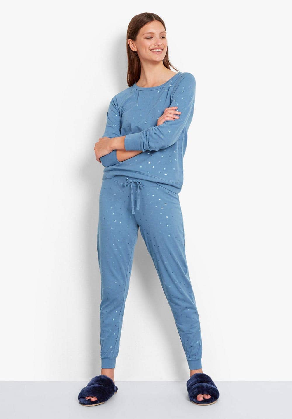 Woman wearing Hush blue jersey and star print pyjamas wiith navy faux fur slipper sliders