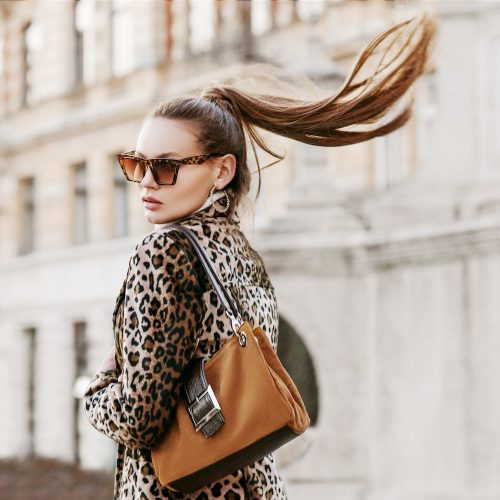 Woman model wearing leopard coat sunglasses with high ponytail