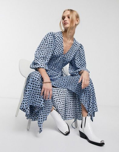 Blonde woman wears Essentiel Antwerp blue and black polka dot wrap dress and white cowboy boota