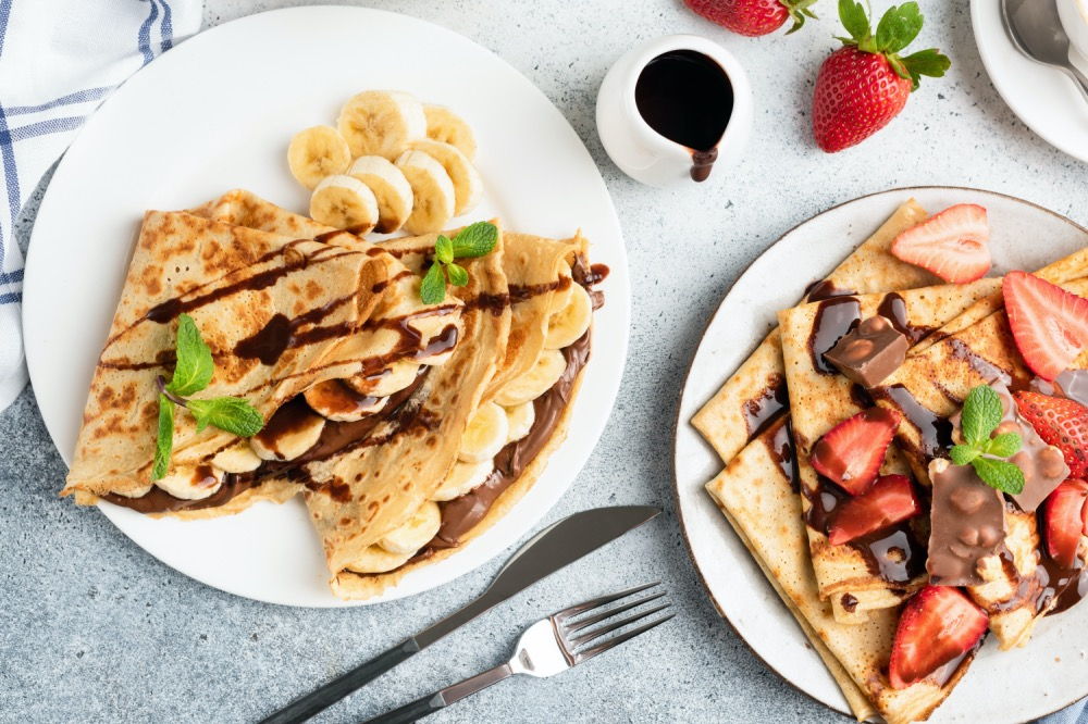 Crepes with chocolate, banana and strawberry. Top view. Tasty European or French style breakfast, table top view