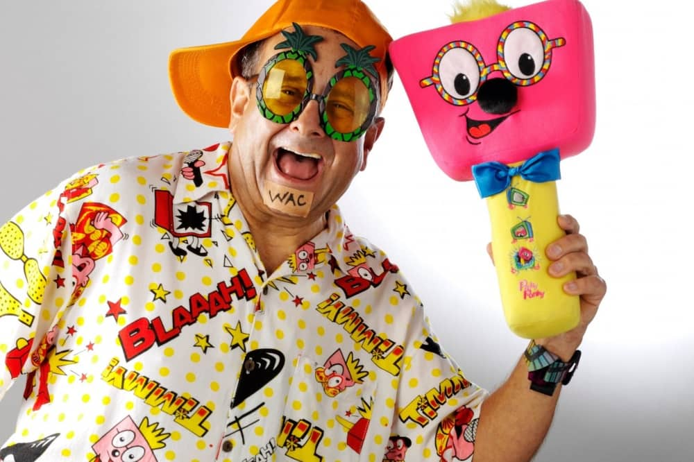 British entertainer timmy mallet in loud shirt, wacky glasses, cap holding a foam mallet