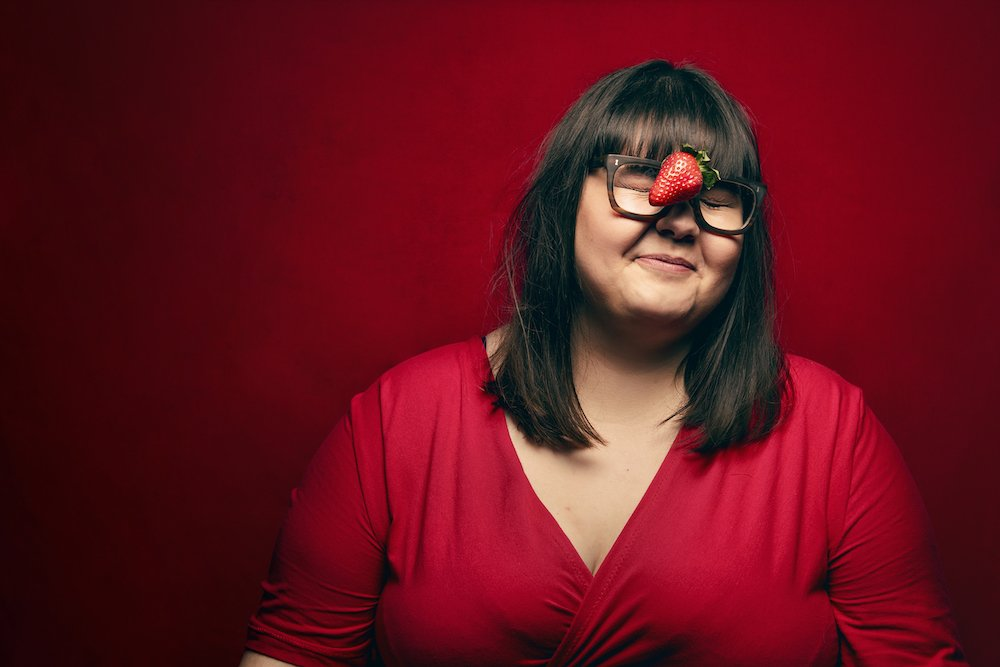 sophie-hagen-the-bumswing women wearing red dress balancing a strawberry on her nose