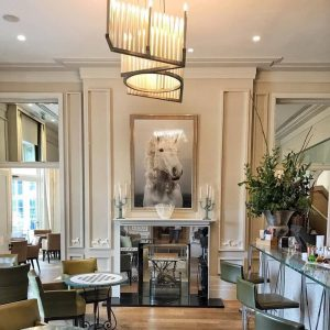 Coworth Park Bar with horse print over fireplace and LOVE chandelier