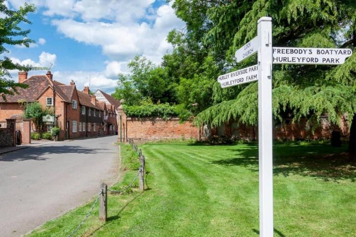 Hurley village red brick period houses, green and white wooden signpost