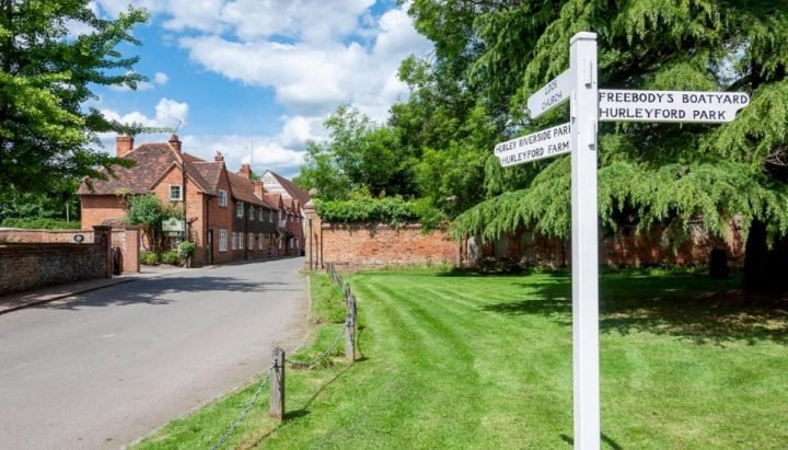 Hurley village near Maidenhead Berkshire read brick period hoouses and traditional white wooden signpost