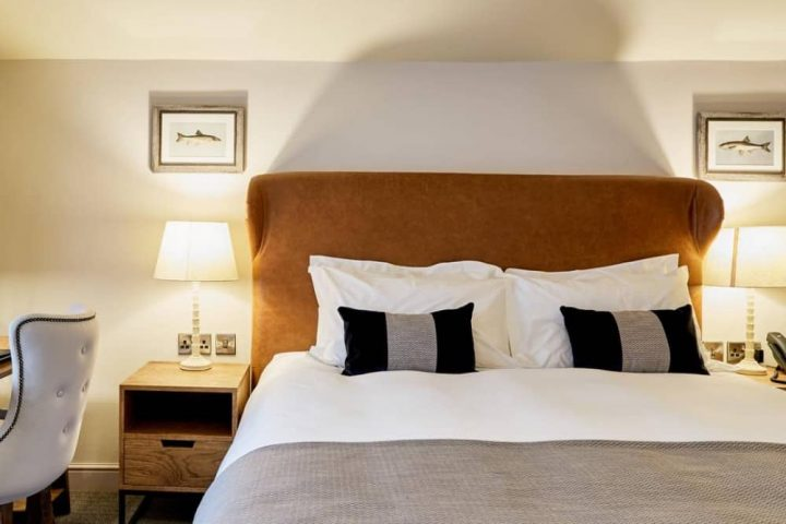 Wellington Arms double bedroom with tan leather headboard and neutral soft furnishings