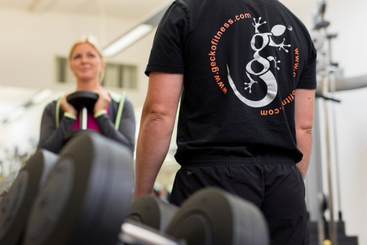 Gecko Fitness instructor in gym with woman lifting weight