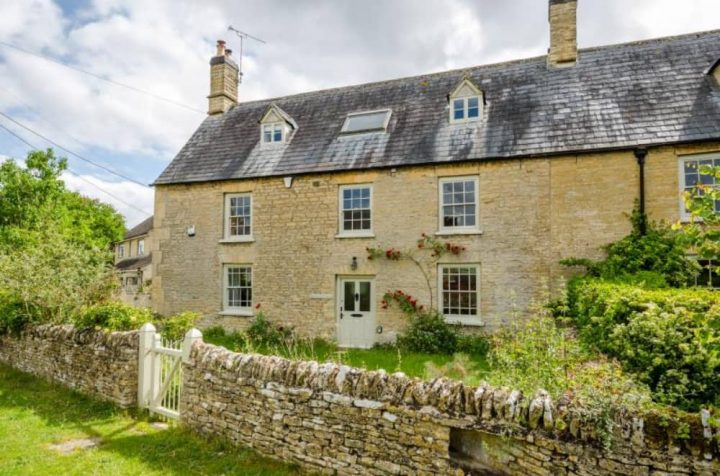 Cotswold gold stone cottage with slate roof and pretty cottage garden