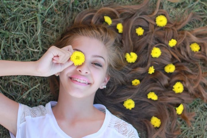 teenager lying in grass ans daisies