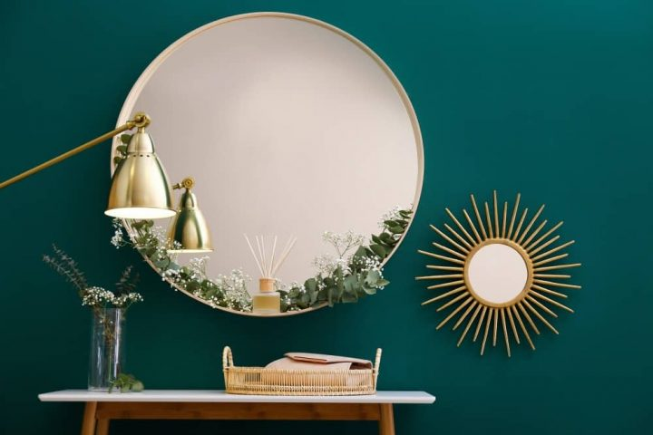 Dark green wall with large round mirror and small sun burst mirror