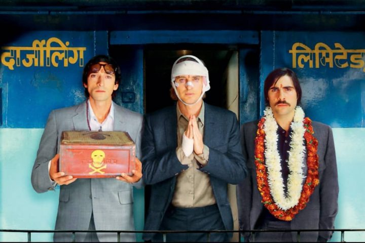 The Darjeeling Limited Owen Wilson Adrien Brody and man with floral garlands stand by Indian train