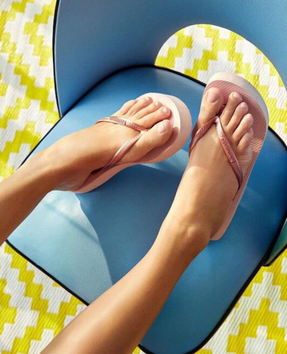 model with feet on blue chair wearing rose gold Havaiana flip flops