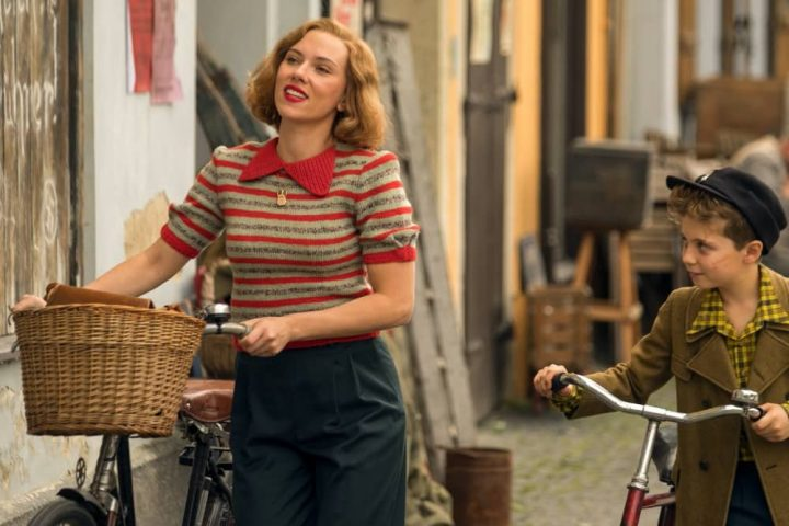 Scarlett Johansson in World War II film Jo Jo Rabbit pushing a retro bike with basket