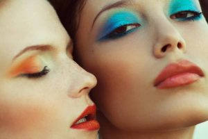 models wearing orange red lipstick with blue and orange eye shadow