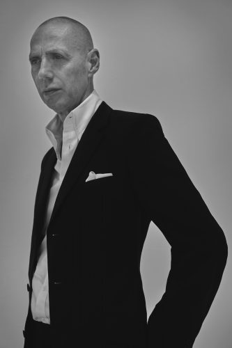 Photographer Nick Knight in black suit and white shirt
