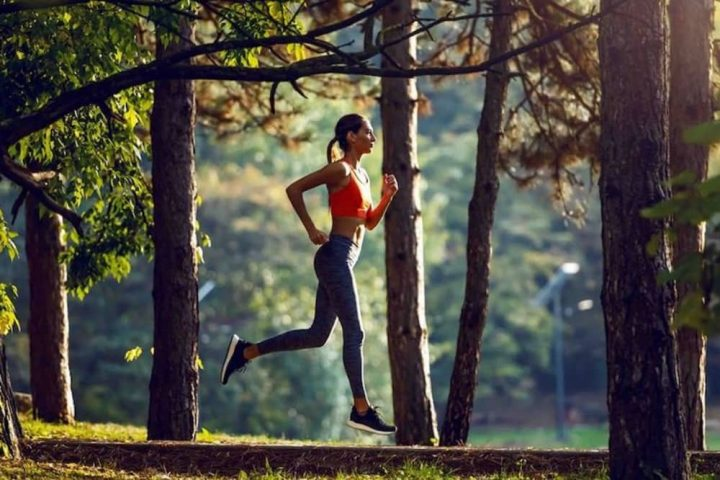 Woman in fitness gear running in woods Stonor Park Henley