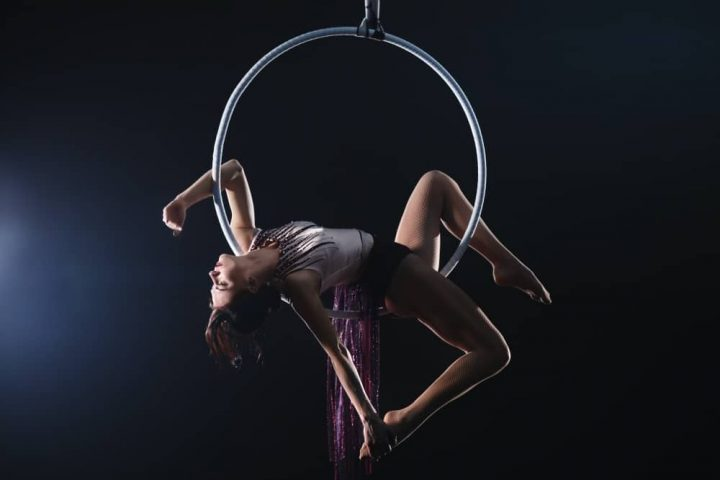 Aerial fitness woman hanging in a hoop