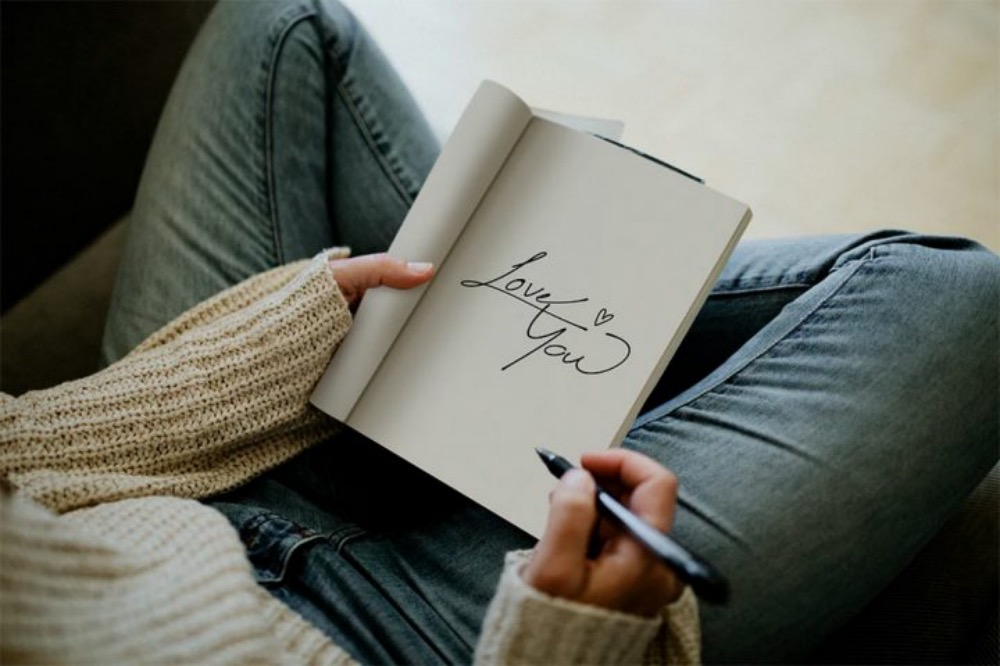 Woman writing love you in a notebook