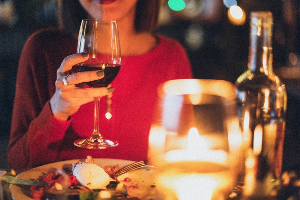 woman at dinner drinking wine