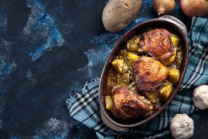 Roasted chicken thighs and potatoes in casserole dish