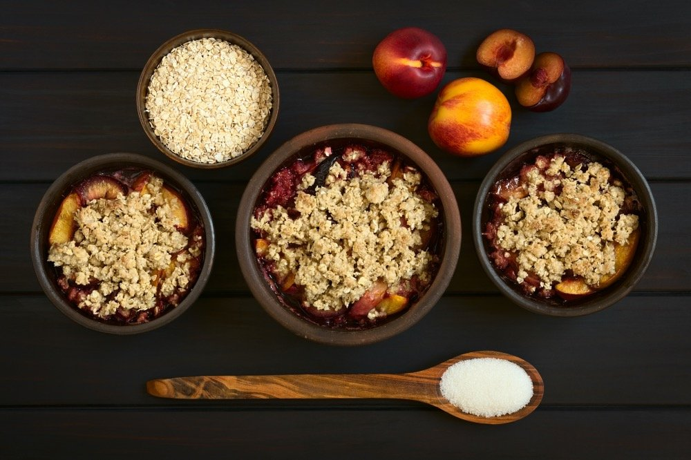 Overhead shot of three rustic bowls filled with baked plum and nectarine crumble or crisp, photographed on dark wood with natural light