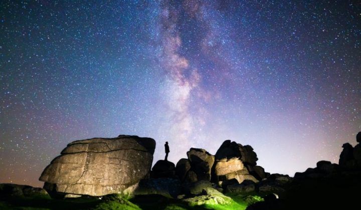 Silhouette of figure stargazing in rocky landscape below a clear night sky & vibrant Milky Way, Dartmoor National Park, UK