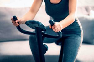 Beautiful athletic girl is engaged on an exercise bike at home, front view, close-up. the concept of exercising or losing weight.