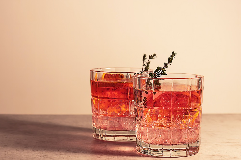 Pink gin cocktail with red blood orange and ice. An alcoholic, refreshing drink