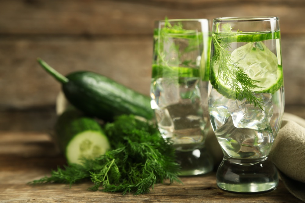 Glasses with fresh organic cucumber drink on wooden table