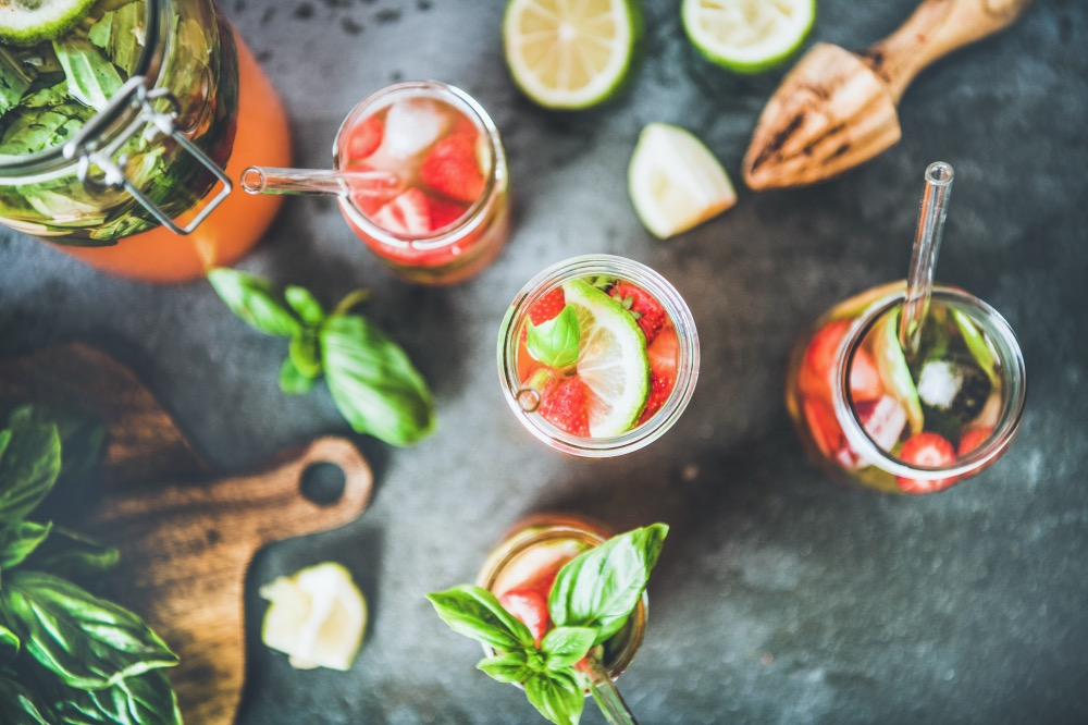 Homemade fresh strawberry and basil lemonade or ice tea in glass tumblers with eco-friendly plastic-free straws over dark grey table background, top view. Cold refreshing summer soft drink