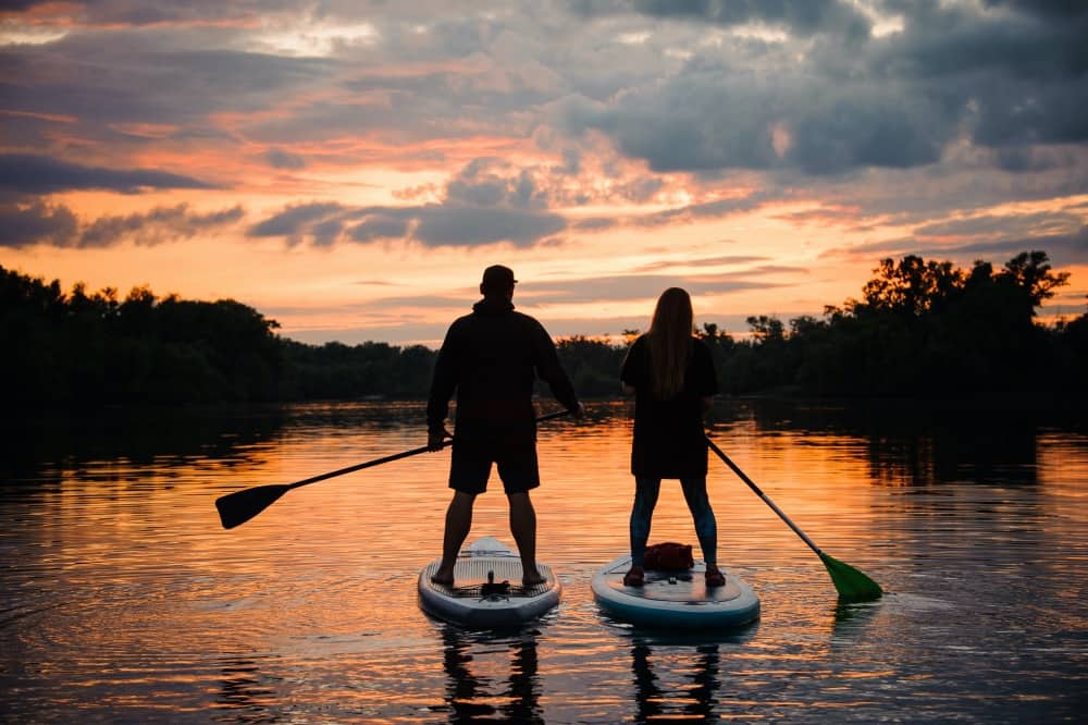 COUPLE paddleboarding SUP at sunset on the river