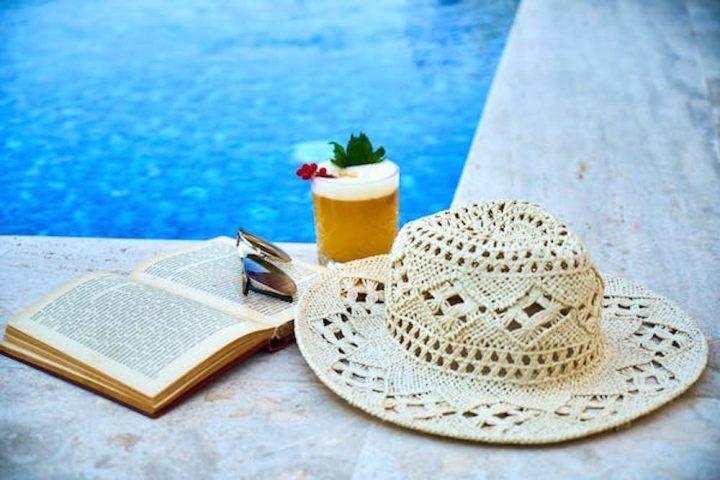 Straw Hat, open book and cocktail by a pool
